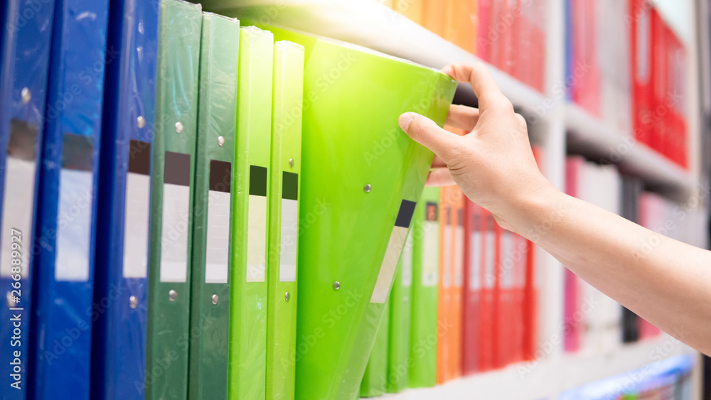 Fototapeta Male hand choosing new green ring binder file folder from colorful shelf display in stationery shop. Buying office supplies concept
