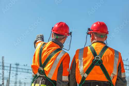 Two workers linemen look on power lines Canvas Print