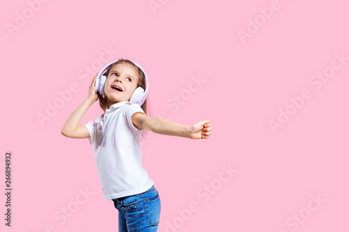 Girl listening to music in headphones on pink background. Cute child enjoying happy dance music, smile, posing on pink studio background wall. - 266894932