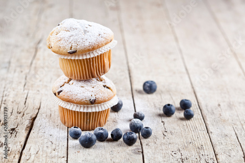 Fototapeta  Two fresh homemade muffins with blueberries on rustic wooden table background