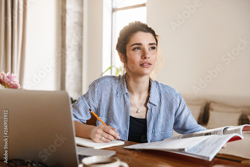 Leinwand Poster Image of candid pretty woman studying with textbooks and using laptop at home