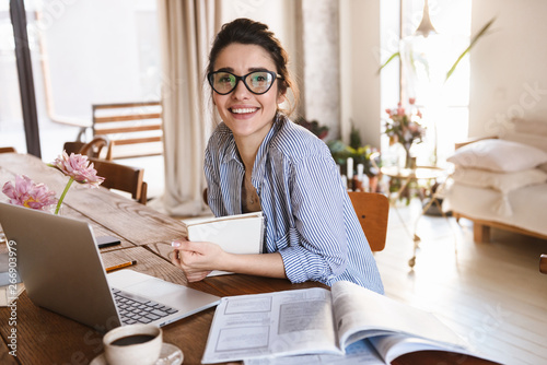 Image of cute young woman 20s typing on laptop while working or studying at home Fototapete