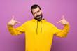 Leinwandbild Motiv Handsome man with yellow sweatshirt proud and self-satisfied