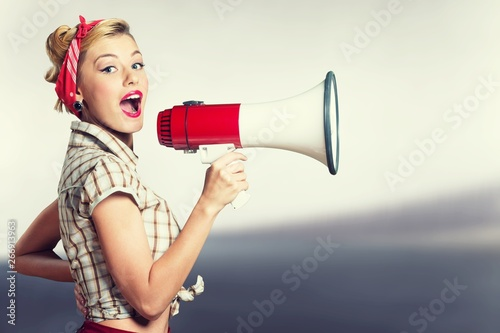 Portrait of woman holding megaphone, dressed in pin-up style - 266913963