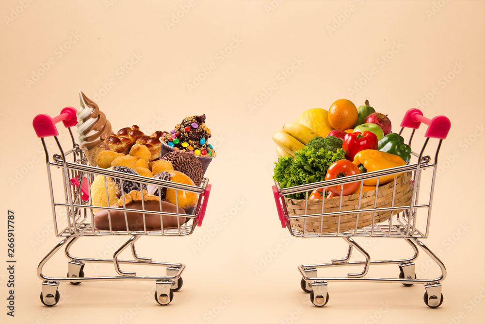 Fototapety, obrazy: Concept of food and diet. Wafers, chocolate, ice cream and fruits and vegetables in shopping cart. Fast food addiction. Struggling with overweight and obesity. comparison between light food and fatten