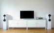 Modern audio stereo system with white speakers on bureau in modern interior