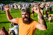 canvas print picture - Open air concert. Fan zone. Music festival. Entertainment concept. Visit summer festival. Summer fest. Hipster in cap happy celebrate event fest or festival. Man bearded hipster in front of crowd
