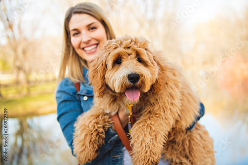 Photographie Happy Labradoodle Dog and woman outside at the park