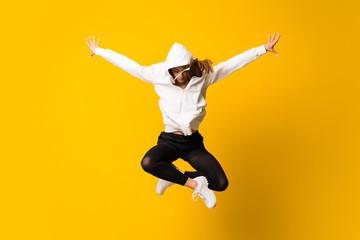 Mlada žena preskačući izolirani žuti zid