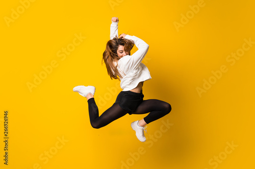 Young woman jumping over isolated yellow wall Fotobehang