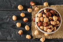 Scattered On The Table Roasted Hazelnuts On A Black Wooden Table. Prepared With The Harvest Of Hazelnuts. Flat Lay.