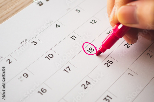 Photo Female Hand with pen mark on calendar date