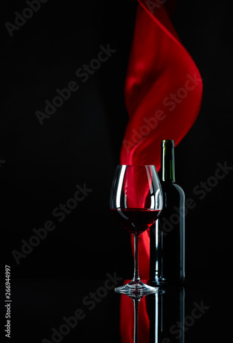 Photo  Wineglass and bottle of red wine on a black reflective background