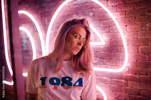 Lovely blonde woman with glasses on the street with neon background Tablou Canvas