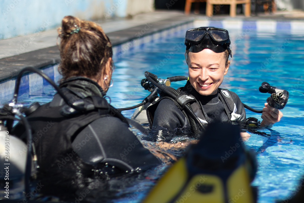 Fototapeta Female diving instructor teaches student to scuba dive in swimming pool. Lady getting first experience with scuba diving under the guidance of experienced recreational diving instructor on vacation.