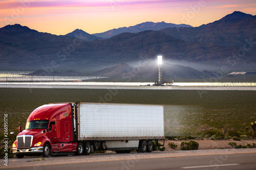 Photographie  An oil and diesel powered truck with solar power plant in the background, clean