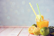 A cool drink of citrus. Orange lemonade in a transparent glass with a straw, next to it are oranges and limes, fresh mint. Copy space.