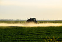 Tractor With The Help Of A Sprayer Sprays Liquid Fertilizers On Young Wheat In The Field.