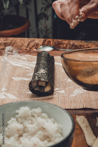 Foto op Aluminium Bier / Cider A female cook prepares sushi in the kitchen and wraps a letter to the nori in the roll