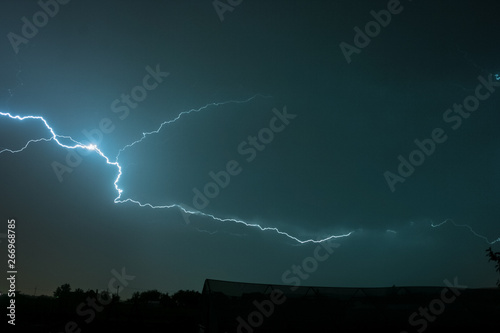Photo  Long bright, capricious lightning bolt travels through the clouds during a sever