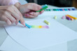 Close-up of female hands are drawing with multicolored chalks on a white sheet, a box with crayons