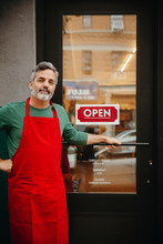 Portrait Of Male Owner Standing By Open Sign At Cafe