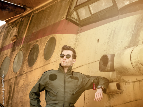 A handsome young pilot standing next to an old plane Canvas Print