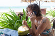 Western girl drinking from a coconut while speaking to the phone, Cuba