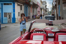 Western Girl Taking Photo With Her Smartphone Of Vintage Cars In Cuba