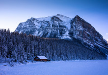 Winter Cabin Next To Forest And Mountains On Snowy Landscape
