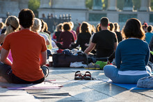Group Of People Sitting In Lotus Position Outdoors.