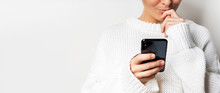 A Young Woman In A White Sweater Holds A Smartphone In Her Hands, Chooses Something Looking At The Screen.