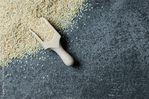 Photo raw sesame seeds in wooden shovel on grey rustic table
