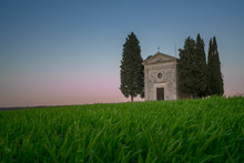 Beautiful Peaceful Landscape Of Small Chapel With Trees In Remote Empty Green Field In Tuscany, Italy