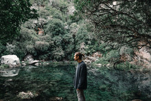 Man Standing Near Calm Pond In Forest