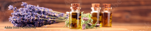 Fotografie, Obraz  essential lavender oil in a glass bottle on a background of fresh flowers
