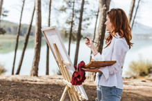 Young Woman Painting In Countr...