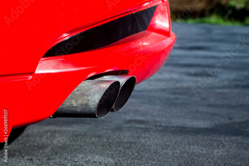 Fotografia  Exhaust pipes from a shiny red sports car with a V8 engine