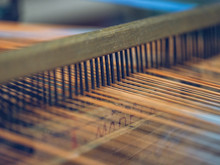 White And Orange Threads On Loom