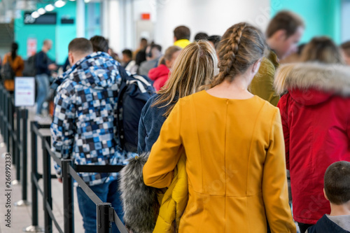 Obraz na plátně Group of anonymous people waiting at airport gate line to board an airplane, queue crowd seen from behind