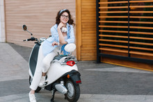 Lovely Young Lady In Vintage Attire Posing On White Scooter With Shy Smile And Holding Big Earphones. Outdoor Portrait Of Blissful Brunette Girl Chilling In Front Of Fashion Boutique On Moped.