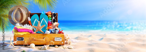 Full Suitcase With Accessories On Tropical Beach - 266996357