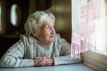 An Elderly Woman Looks Out The Window Sitting In His House. Care Of Lonely Pensioners.