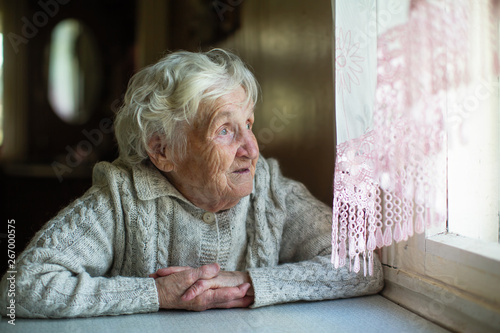 Obraz An elderly woman looks out the window sitting in his house. Care of lonely pensioners. - fototapety do salonu