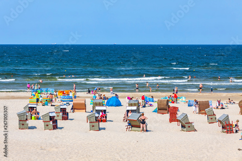 Obraz Unrecognisable people relax on a Baltic sea beach on Usedom island in Swinoujscie city, Poland - fototapety do salonu
