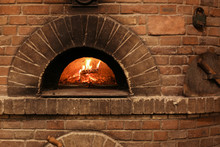 Brick Oven With Burning Firewood And Pizzas Indoors