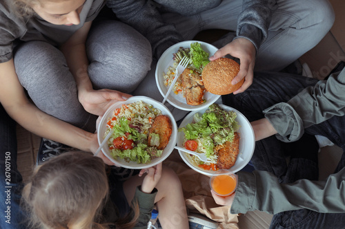 Foto op Canvas Kruidenierswinkel Poor people with plates of food sitting on floor indoors, view from above