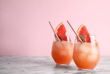 Glasses Of Grapefruit Cocktails On Table Against Color Background. Space For Text