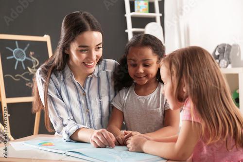 Canvas Print Cute little children with nursery teacher reading book at table in kindergarten