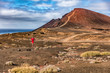 canvas print picture - Athlete runner man trail running on volcanic mountain background terrain. Sports and fitness. Hero shot on nature landscape.